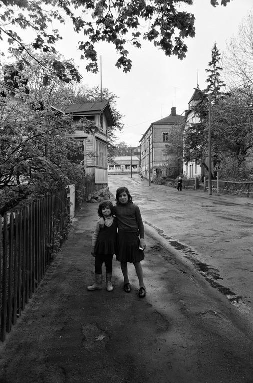 Kaksi tyttöä sateen kastelemalla Hertankadulla puutalojen Länsi-Pasilassa. Kesä 1974. Vasemmalla Hertankatu 12, oikealla Hertankatu 11, 13. Keskellä siintää Elannon liikerakennus (Hertankatu 15, Elannon myymälä lopetti toimintansa 22.6. 1979.)