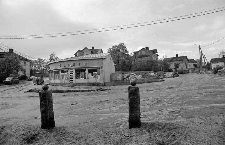 Kiviset portin pylväät, vasemmalla Elannon myymälärakennus Hertankatu 15:ssä sekä oikealla Eevankadun puutaloja Länsi-Pasilassa. Kesä 1974. Kuvattu Susannankadulta käsin.
